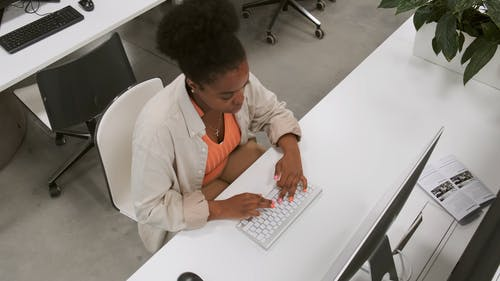 A Woman Works On A Computer Inside An Office