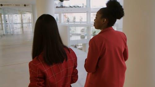 Due Donna Che Parla Mentre Si Cammina In Un Corridoio
