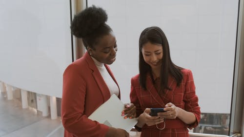 A Woman Share Something In Her Cellphone To another Woman Before They Step Out From The Elevator