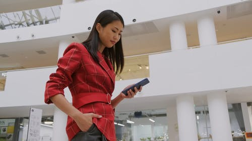 A Woman Checks Her Phone While Walking Inside A Mall
