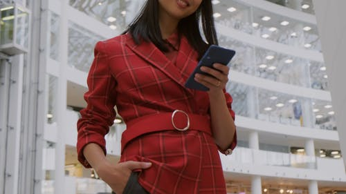A Woman With A Phone On Hand Smiling For The Camera