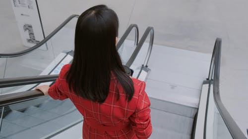 A Woman With A cup On Hand Turns Her Back And Gives A Smile In An Escalator Going Down