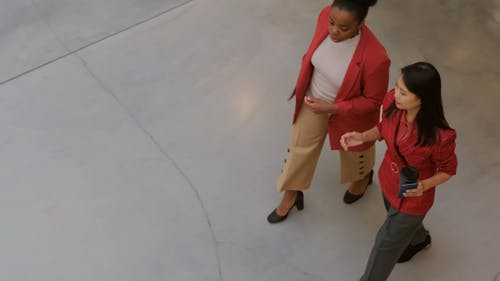 Two Women In A Business Discussion While Walking