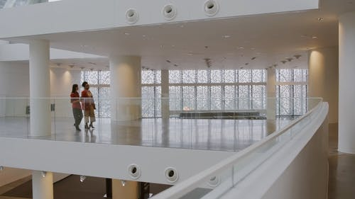 Two Women Walking In The Hall Of A Building While Having A Conversation