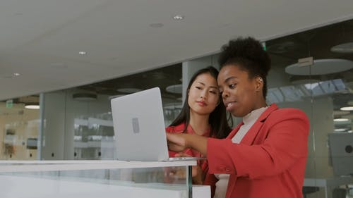 Two Women With A Laptop Sharing Ideas About Work