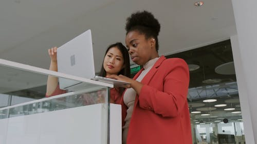 A Woman Using A Laptop On A Ledge While Another Woman Assisting Her By Holding It