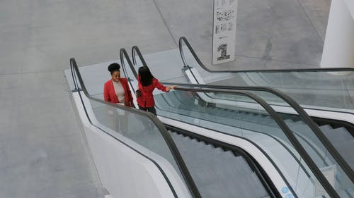 Two Woman Having Conversation On Escalator Going Up