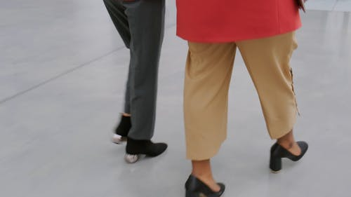 Two Women Walking Towards The Escalator To Go Up