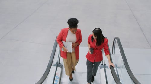 Two Women Having A Conversation While On An Escalator
