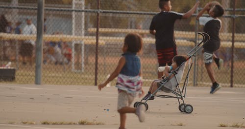 A Toddler Drinking From A Milk Bottle On A Stroller Parked Close To Children Playing Basketball IN A Ballpark