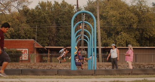 Kids Enjoying The Swings In A Playground While Mothers Are On Guard