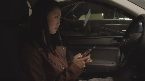 Woman On The Driver's Seat Of A Car Smiling While Texting