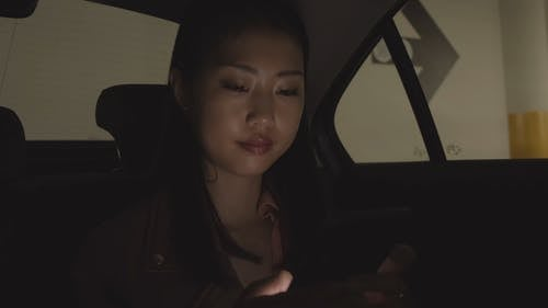 Woman Using Her Phone In The Dark