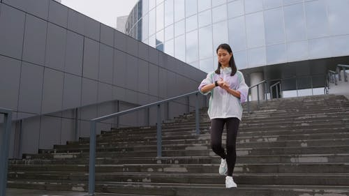 Woman Going Down The Stairs While Tracking Her Steps