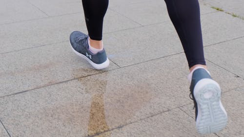 A Person Running On A Wet Concrete Pavement
