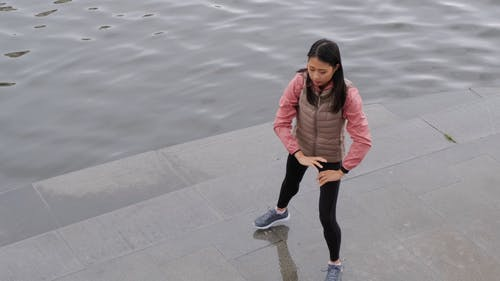 A Woman Does Body Stretches Exercise Along The Riverbank