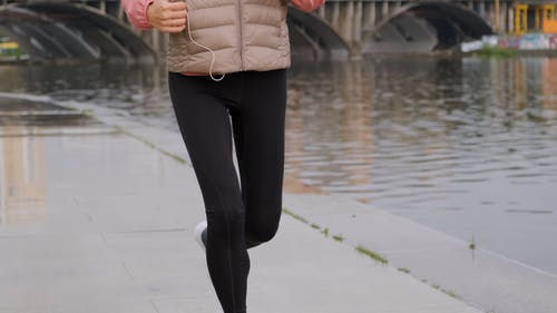 A Person Jogging On The Riverbank