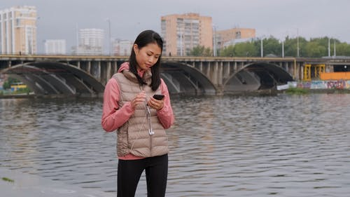 A Woman Setting Her Phone And Wearing Her Ear Phones Before Going For A Jog