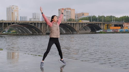 A Woman Doing Jumping Exercises Along The River Banks
