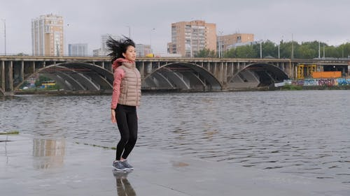 A Woman Doing Jumping Exercises By The Riverside