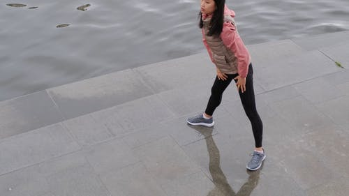 A Woman Doing Stretch Exercises By The Riverbank