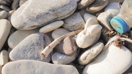 A Crashed Plastic Bottle Lies Over A Pile Of Cobblestones