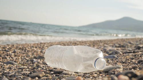 Close-up Of A Discarded Plastic Bottle On The Rocky Shore With The Waves Breaking In Slow Motion