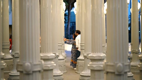 A Couple Taking Selfie Photos Using A Smartphone Besides A Row Of Concrete Cast Pillars