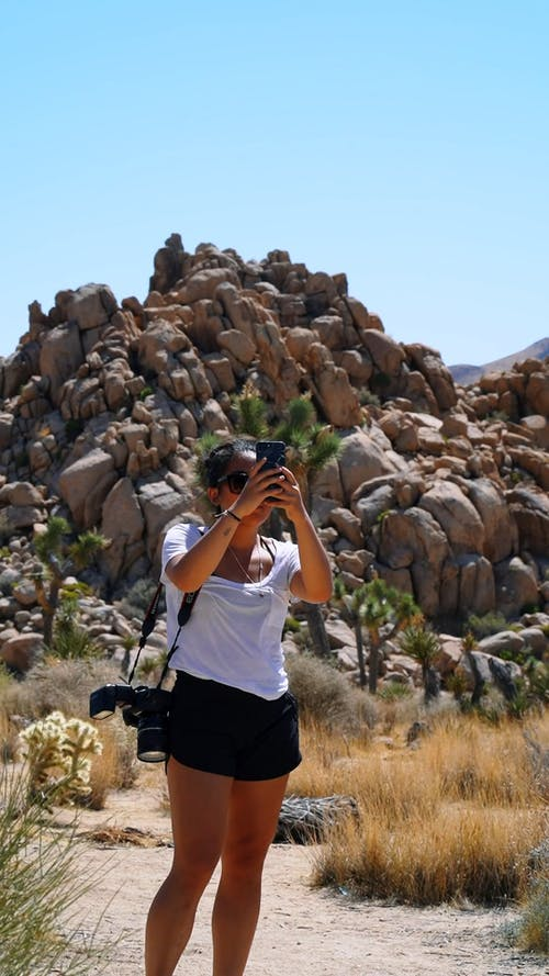 A Woman Taking A Full Turn Video Footage Of The Desert Surrounding Using Her Smart Phone