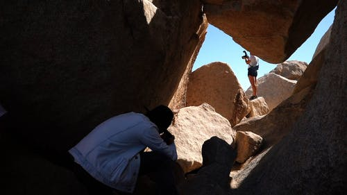 Low Angle Footage Of Two Photographers Taking Pictures Of Huge Boulders And Rock Formations