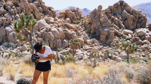 A Woman Taking A Photo In A Hot And Rocky Area
