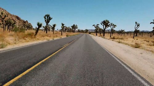 Fast Motion Footage Of Vehicles On A Road With The View Of The Desert Landscape At Daytime