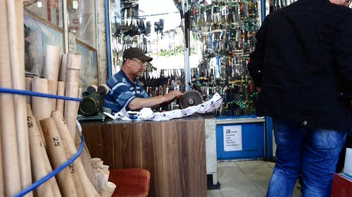 An Elderly Man Sitting Behind A Work Table Sharpening A Knife With A Machine Inside A Store