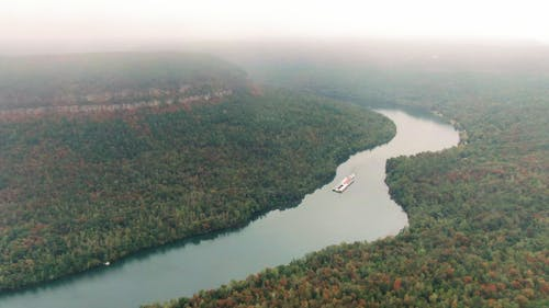 Aerial Footage Of A Barge Traversing A River Surrounded By Thick Forest And AMountain