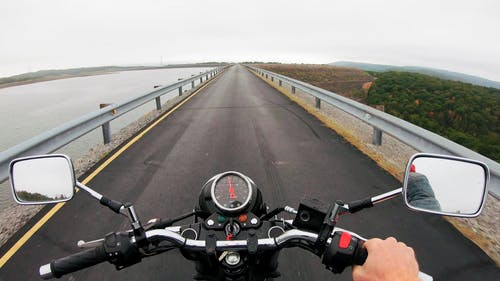 A Motorcycle Rider Traveling On The Dam Wall Built As Road