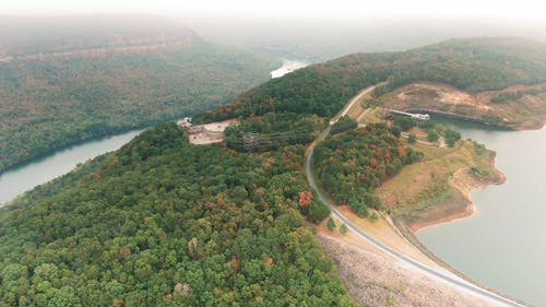 Aerial Footage Of A Reservoir On Top Of A Mountain With Lush Vegetation And River Below