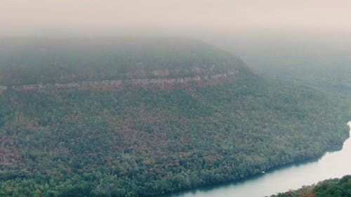 Foggy Footage Of A River Across The Mountain Forest