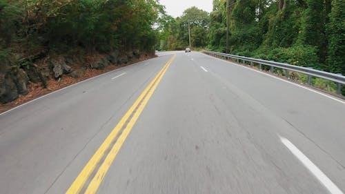 A Biker Traversing A Road Built On Mountain Sides