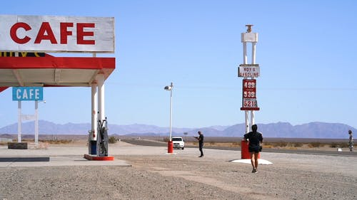 People And Vehicular Traffic Of A Rest Stop Area Along The Desert Hi-way