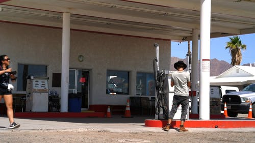 A Man And A Woman Taking Pictures Using Their Digital Cameras While In A Gasoline Station