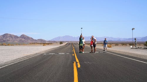 A Group Of People Taking Selfie Photos In The Middle Of An Empty Road