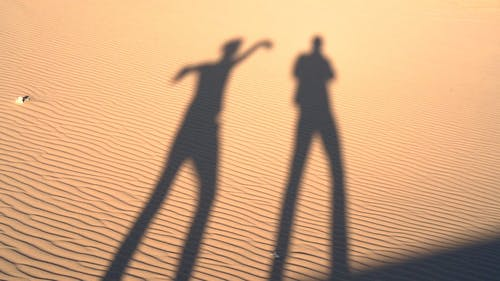 Shadows Of  People On A Desert Sand
