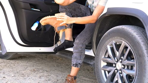 Slow Motion Footage Of A Person Sitting In An Open Door Vehicle Cleaning The Sand Off Inside His Leather boots