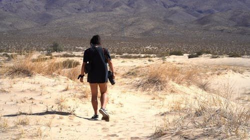 Woman Walking In The Desert On A Hot Day