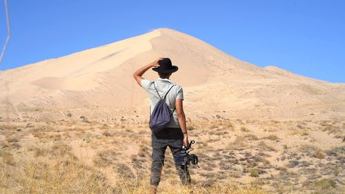 Back View Of A Man Holding A Camera Standing In Front Of A Sand Dune In The Dessert