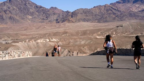 People Walking On The Road Enjoying The View Of Mountain Ranges