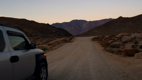 Lone Vehicle Traveling A Unpaved Road In The Desert With A View Of The Mountains