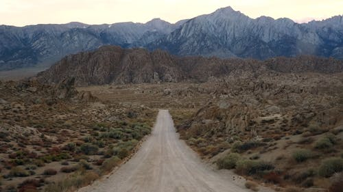 An Off Road Leading To The Rocky Hills And Mountains