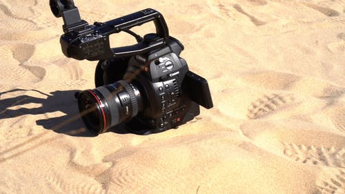 A Modern Digital Camera Lying On The Desert Sand