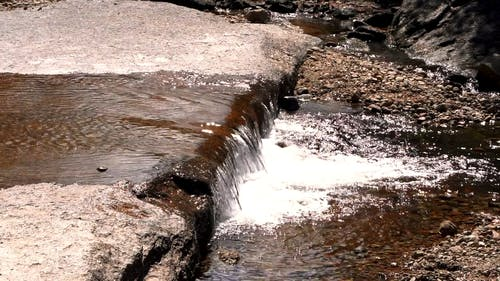 A Narrow And Shallow River Streaming Through The Bed Of Rocks